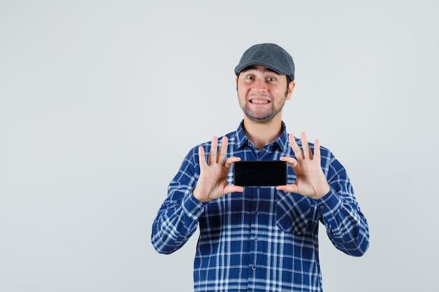 Junger mann, der foto auf handy in hemd, mütze und fröhlich, vorderansicht nimmt.