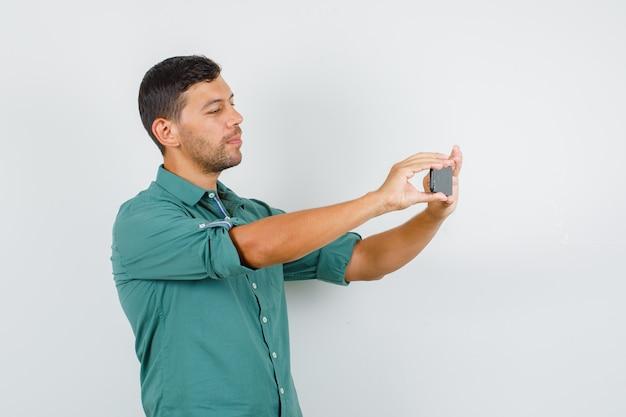 Junger mann, der foto auf smartphone im hemd nimmt