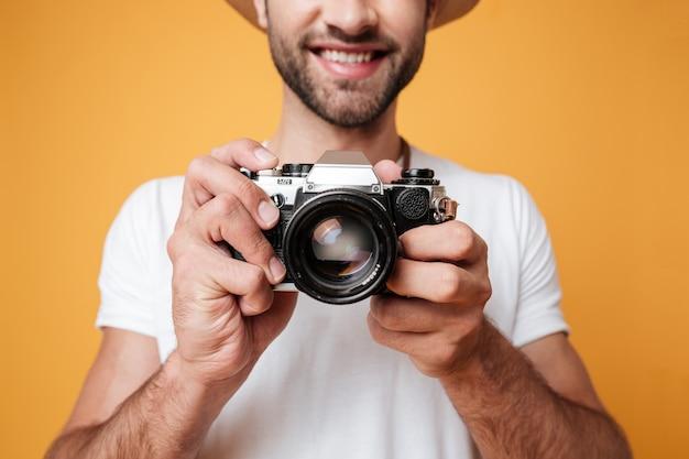 Junger mann, der foto mit retro-kamera macht