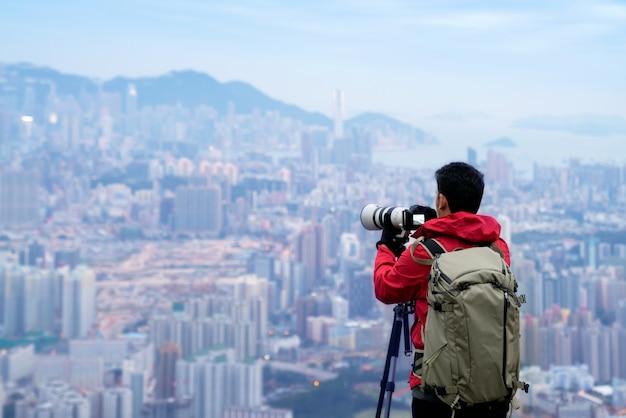 Junger mann, der foto mit seiner kamera mit stativen im berg mit stadt macht