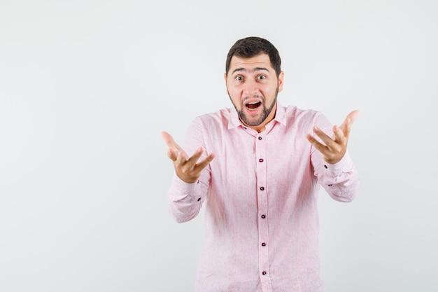 Junger mann, der fragend hände im rosa hemd erhebt und erstaunt schaut