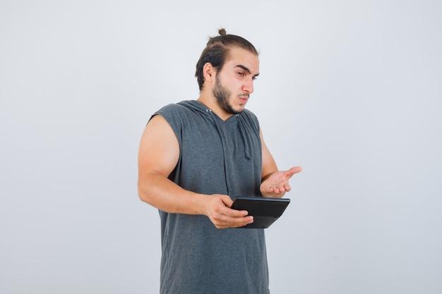 Junger mann, der fragende geste im kapuzenpulli macht und verwirrt schaut.