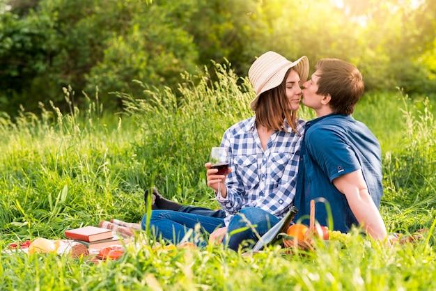Junger mann, der frau auf picknick küsst