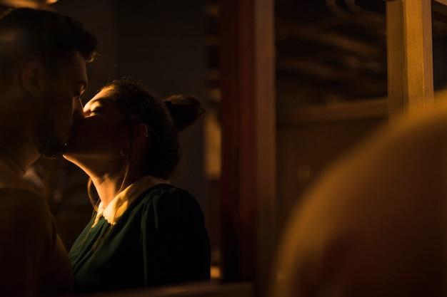 Junger mann, der frau in der dunkelheit küsst