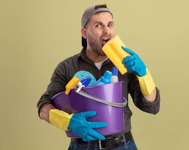 Junger mann, der freizeitkleidung und kappe in den gummihandschuhen trägt, die eimer mit reinigungswerkzeugen und schwamm wütend und verrückt wahnsinnig gehender wilder beißender schwamm hält über grüner wand