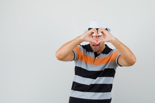 Junger mann, der friedensgeste über seinem auge in t-shirt, hut zeigt und geliebt aussieht. vorderansicht.