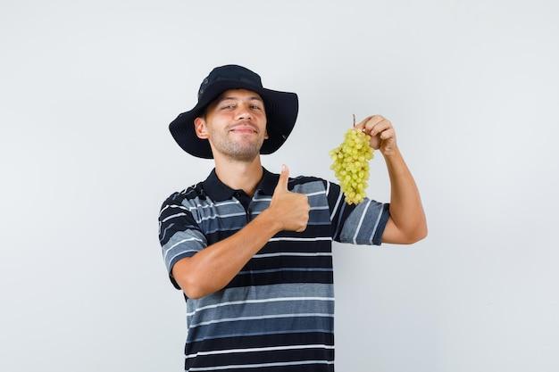 Junger mann, der frische trauben mit daumen nach oben in t-shirt, hut hält und fröhlich aussieht. vorderansicht.