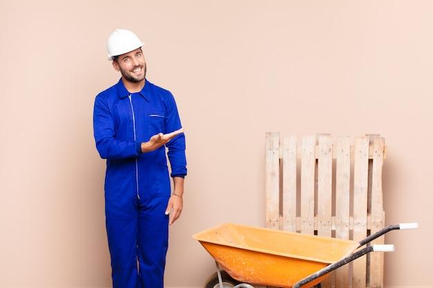 Junger mann, der fröhlich lächelt, sich glücklich fühlt und ein konzept im kopierraum mit handflächenkonstruktionskonzept zeigt