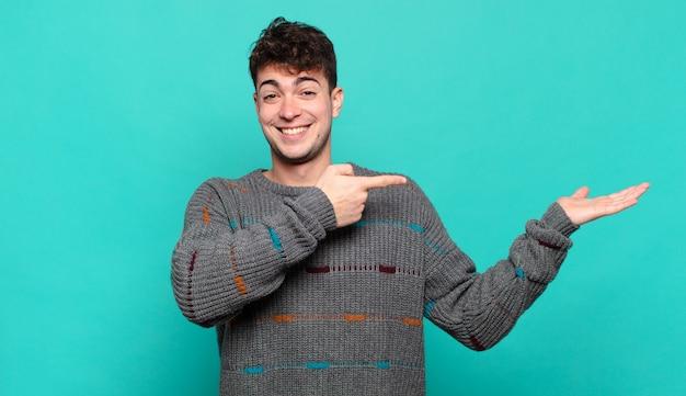 Junger mann, der fröhlich lächelt und zeigt, um platz auf handfläche auf der seite zu kopieren, ein objekt zeigend oder werbend