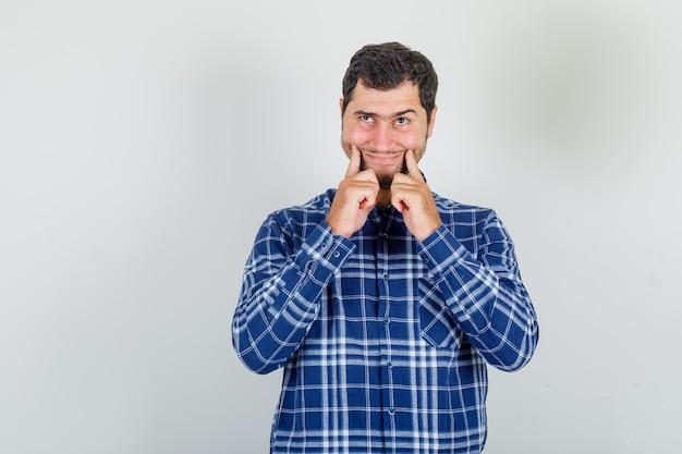 Junger mann, der fröhliches lächeln im karierten hemd erzwingt und missfallen aussieht