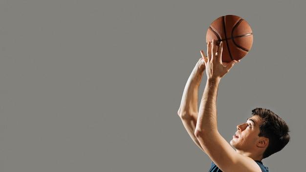 Junger mann, der für basketballspiel mit kopienraum trainiert