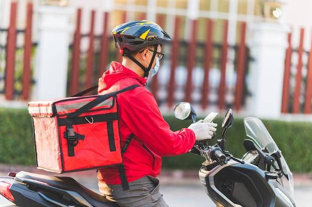 Junger mann, der für einen lebensmittel-lieferservice arbeitet, der mit straßenmotorrad in der stadt prüft