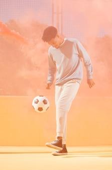 Junger mann, der fußball spielt
