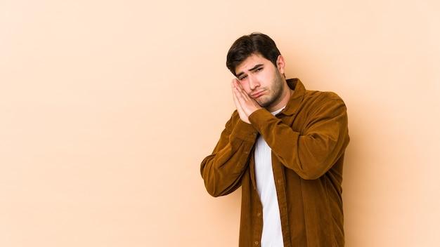 Junger mann, der gähnt und eine müde geste zeigt, die mund mit hand bedeckt.