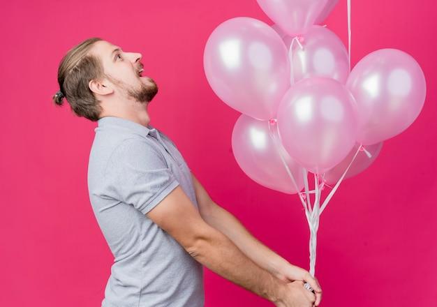 Junger mann, der geburtstagsfeier feiert, die bündel luftballons hält, die seitlich stehen und glücklich und aufgeregt über rosa wand schauen