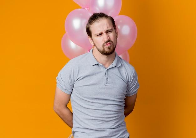 Junger mann, der geburtstagsfeier feiert, die bündel luftballons hält, die unzufrieden und unglücklich beiseite stehen und über orange wand stehen