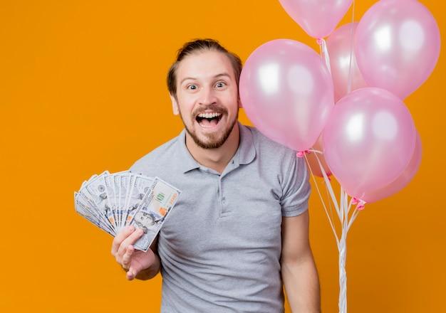 Junger mann, der geburtstagsfeier feiert, die bündel von luftballons hält, die bargeld glücklich und aufgeregt über orange wand stehend zeigen