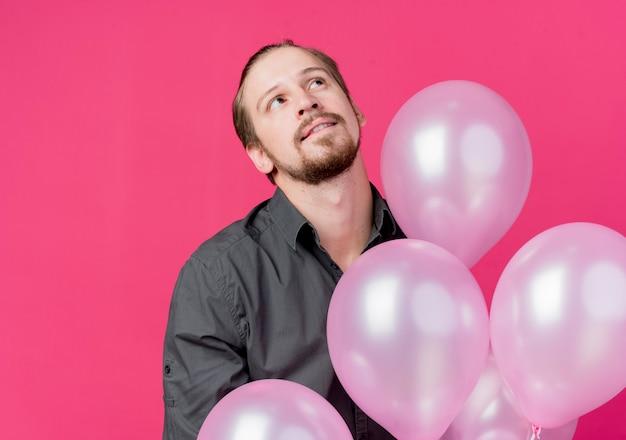 Junger mann, der geburtstagsfeier feiert, die bündel von luftballons hält, die mit nachdenklichem ausdruck denken, der über rosa wand steht