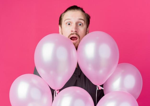 Junger mann, der geburtstagsfeier feiert, die über luftballons späht, erstaunt und überrascht, über rosa wand stehend