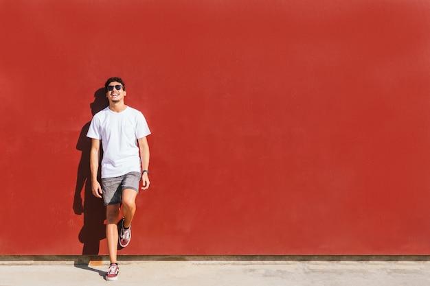 Junger mann, der gegen eine rote wand lächelt
