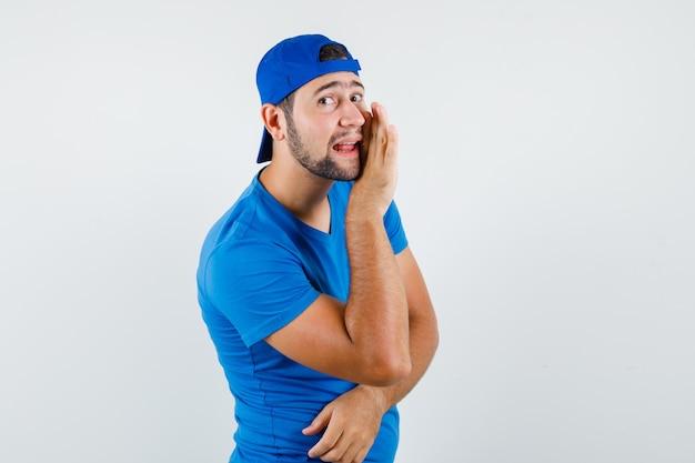 Junger mann, der geheimnis hinter hand in blauem t-shirt und mütze erzählt und klatschig schaut