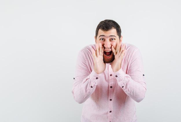 Junger mann, der geheimnis mit händen nahe mund im rosa hemd erzählt und optimistisch schaut