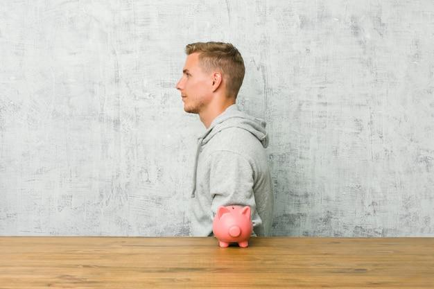 Junger mann, der geld mit einem sparschwein nach links anstarrt, werfen seitlich auf.