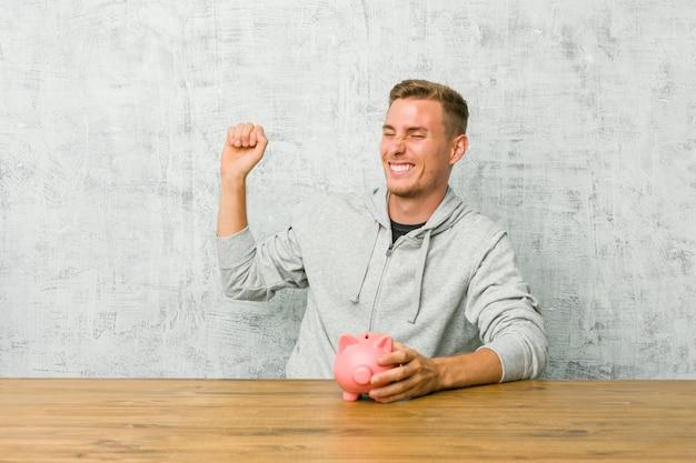 Junger mann, der geld mit einem sparschwein tanzt und spaß hat.