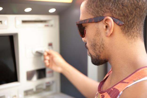 Junger mann, der geld vom geldautomaten abhebt