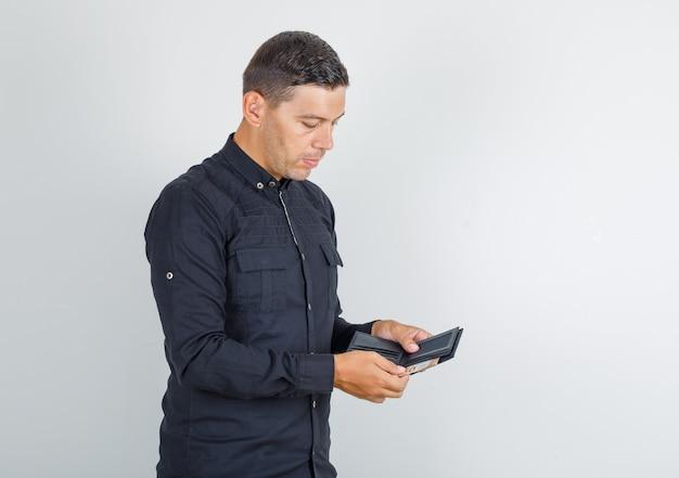Junger mann, der geld von der brieftasche im schwarzen hemd herausnimmt.