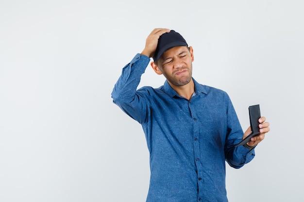 Junger mann, der geldbörse im blauen hemd, in der kappe hält und vergesslich schaut, vorderansicht.