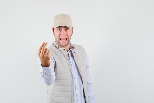 Junger mann, der geldgeste zeigt, zunge in beige jacke und mütze herausstreckt und glücklich schaut. vorderansicht.