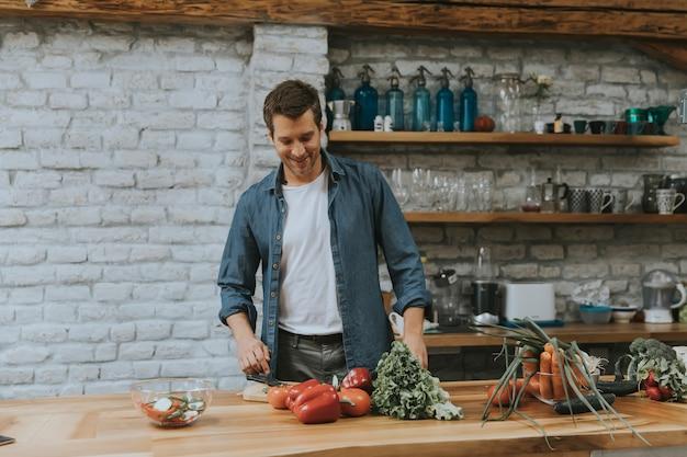 Junger mann, der gemüse in der küche hackt und gesunde mahlzeit zubereitet