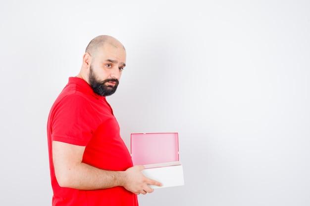 Junger mann, der geöffnete geschenkbox im roten t-shirt hält und nachdenklich schaut, vorderansicht.