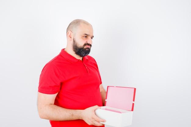 Junger mann, der geöffnete geschenkbox im roten t-shirt hält und unzufrieden aussieht, vorderansicht.