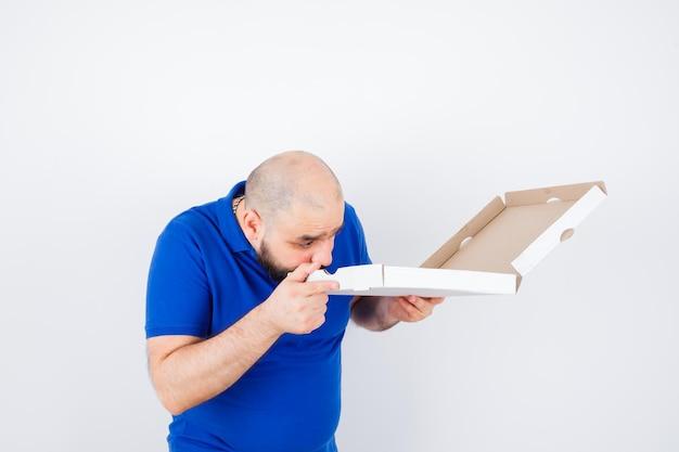 Junger mann, der geöffnete pizzaschachtel im t-shirt betrachtet und sich wunderte, vorderansicht.