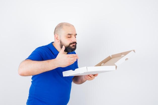 Junger mann, der geöffnete pizzaschachtel im t-shirt riecht und erfreut aussieht, vorderansicht.