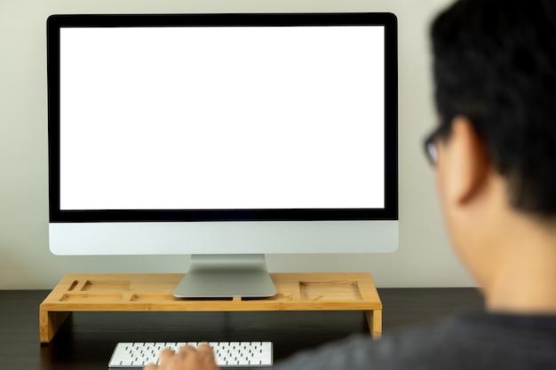 Junger mann, der geschäftsmann mit einem desktop-computer des leeren bildschirms arbeitet