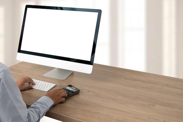 Junger mann, der geschäftsmann unter verwendung eines desktop-computers des leeren bildschirms arbeitet