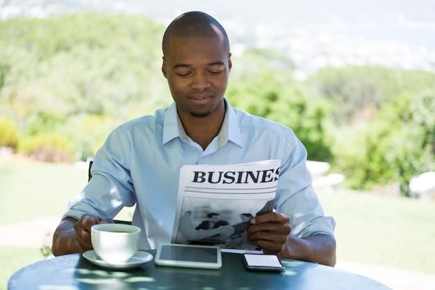 Junger mann, der geschäftszeitung im restaurant liest