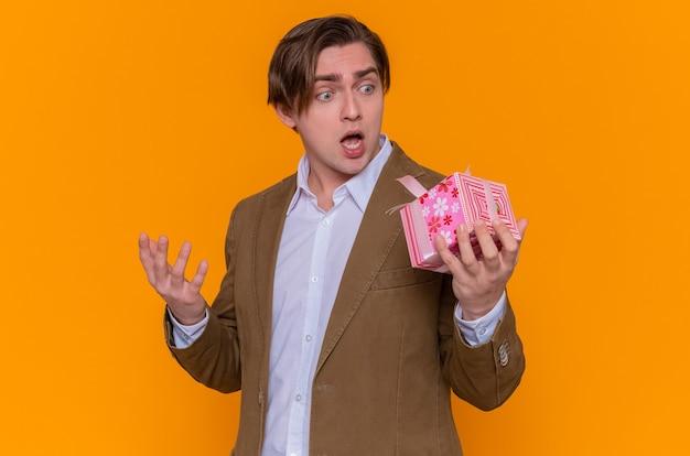 Junger mann, der geschenk hält und es betrachtet, erstaunt und überrascht, zum internationalen frauentag zu gratulieren, der über der orangefarbenen wand steht Kostenlose Fotos