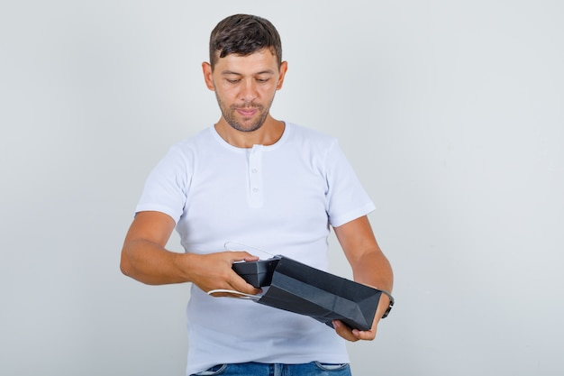 Junger mann, der geschenkbox aus tasche in weißem t-shirt, jeans vorderansicht nimmt.