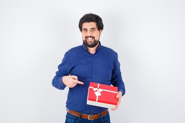 Junger mann, der geschenkbox hält und darauf in blauem hemd und jeans zeigt und optimistisch aussieht, vorderansicht.