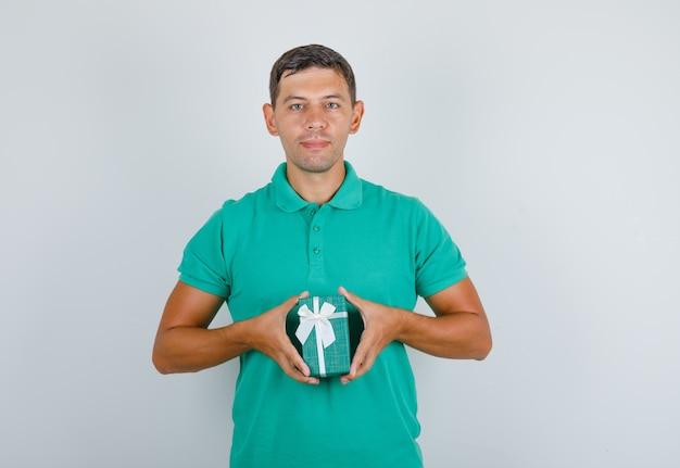 Junger mann, der geschenkbox hält und im grünen t-shirt, vorderansicht lächelt.