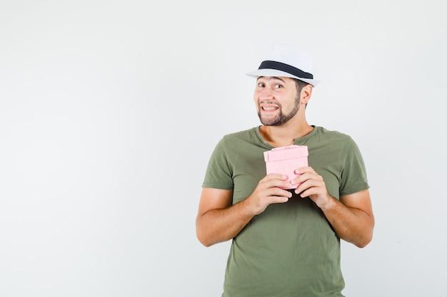 Junger mann, der geschenkbox im grünen t-shirt und im hut hält und niedlich schaut