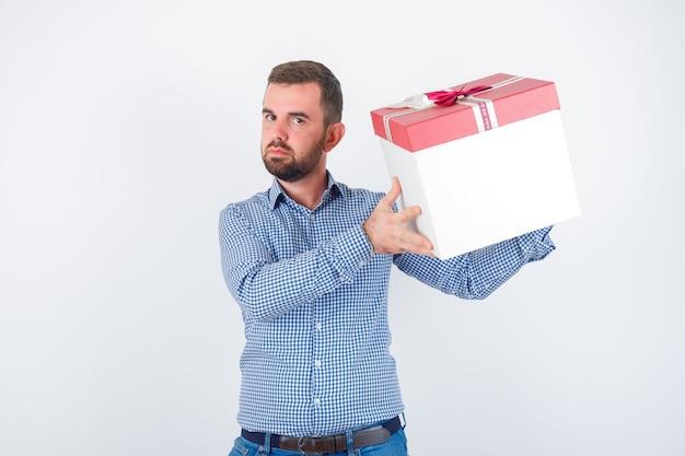 Junger mann, der geschenkbox im hemd hält und fokussierte vorderansicht schaut.