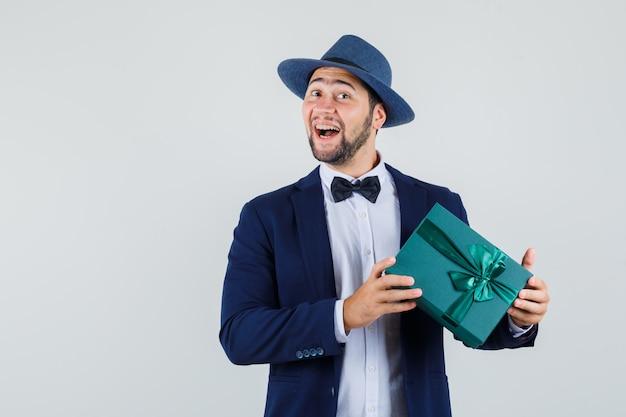 Junger mann, der geschenkbox in anzug, hut hält und glücklich schaut. vorderansicht.