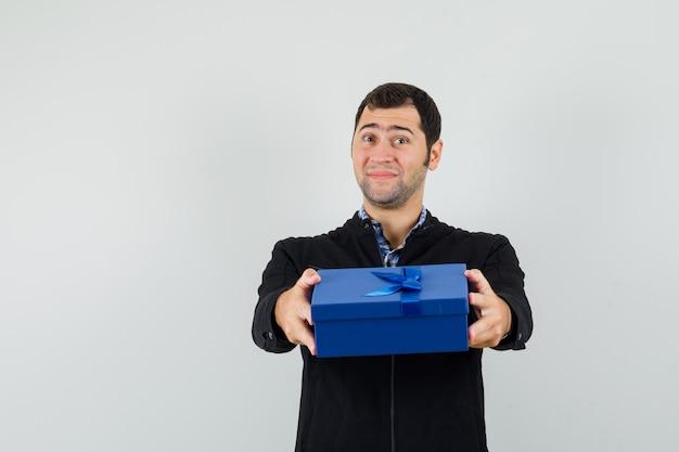 Junger mann, der geschenkbox in hemd, jacke präsentiert und sanft, vorderansicht schaut.
