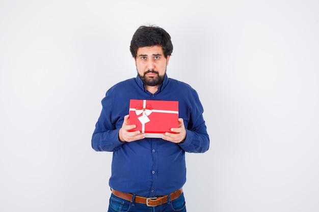 Junger mann, der geschenkbox mit beiden händen in blauem hemd und jeans hält und ernst schaut, vorderansicht.