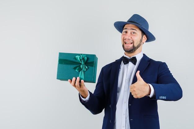 Junger mann, der geschenkbox mit daumen oben in anzug, hut hält und froh aussieht. vorderansicht.